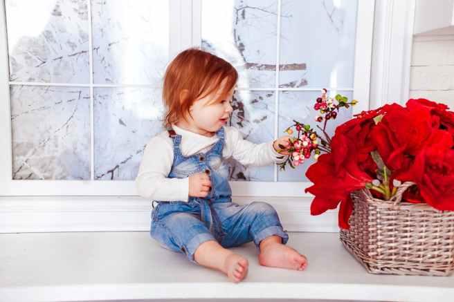 kid s blue denim jumper sitting on white wooden side table
